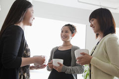 Three businesswomen on the coffee break in the office Stock Photos