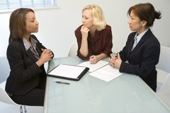 Three businesswomen at desk. Three businesswomen sitting at a desk in a white office in a meeting royalty free stock image