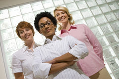 Three businesswomen by glass block wall, one with arms crossed, smiling, portrait, low angle view Royalty Free Stock Photo