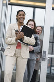 Three businesswomen leaving an office building. Stock Image