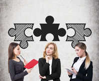 Three businesswomen and matching puzzle pieces. Three young businesswomen are standing near a concrete wall with three matching puzzle pieces above their head Stock Photography