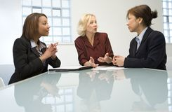 Three businesswomen in meeting. Three businesswomen in a meeting, discussing some documents royalty free stock photography