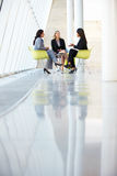 Three Businesswomen Meeting Around Table In Modern Office Stock Photo