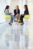 Three Businesswomen Meeting Around Table In Modern Office Stock Image
