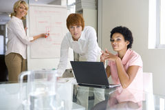 Three businesswomen in meeting room, one at laptop, one by flipchart, smiling, portrait Royalty Free Stock Photography