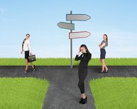 Three businesswomen and road sign Stock Photos
