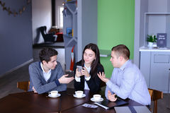 Three busy company employees, two young men and woman busy with Stock Image