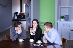 Three busy company employees, two young men and woman busy with Royalty Free Stock Photos
