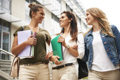 Three busy students on campus Royalty Free Stock Image