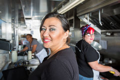 Three Busy Workers inside  a Food Truck Royalty Free Stock Images