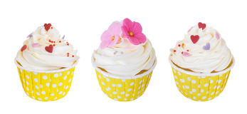Three butter cream cupcakes with sweet flowers and hearts in polka dot paper cup isolated on white background, path Royalty Free Stock Photography