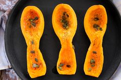 Three butternut squash pieces with pumpkin seeds on black tray Stock Photos