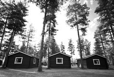 Three cabins in woods. A black and white view of three rustic cabins in the woods royalty free stock photos