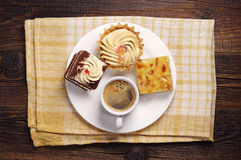 Three cakes and coffee cup. In white plate on a yellow tablecloth. Top view Stock Image