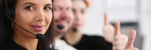 Three call centre service operators arm show OK Stock Images