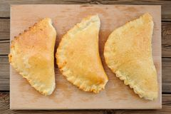 Three calzone pizzas on wooden board top view Stock Image