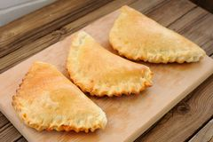 Three calzone pizzas on wooden plank Stock Images