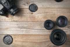 Three camera lenses and a dslr digital camera on a wooden table, top view. Camera lenses and a dslr digital camera on a wooden table, top view stock images