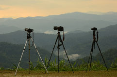 Three camera tripods photographer sunset. Stock Images