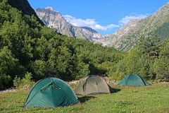 Three camping tents between the mountains. Three camping tents in the ravine of Bilyagidon river between the mountains of Digoria in the morning, Caucasus Royalty Free Stock Photo