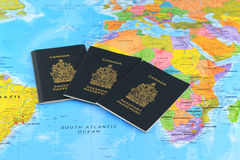 Three Canadian Passports on the world map Royalty Free Stock Photos