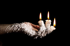 Three candle sticks on fingers buring artistic conversion Royalty Free Stock Photos