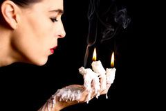 Three candle sticks on fingers buring face blow artistic convers Stock Image