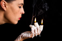 Three candle sticks on fingers buring face blow Stock Images