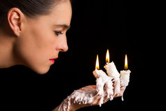 Three candle sticks on fingers buring with wax flow face blow Royalty Free Stock Photos