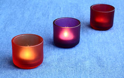 Three candles. Three burning candles on a jean cloth Stock Photography