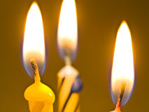 Three candles. On yellow background Royalty Free Stock Photography