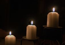 Three candles. Candles burning in the dark stock photography