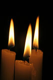 Three candles. Burning in the dark Stock Photos