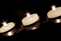 Three Candles. Three lit votive candles in a long holder.  Diagonally placed in the frame. Black background Stock Photography