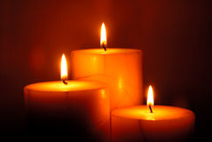 Three candles. Illuminating a dark room Stock Images