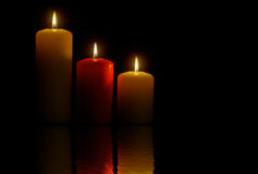 Three Candles. Over a black background and its reflection Royalty Free Stock Photography