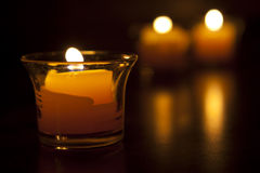 Three Candles. Burning with reflection and out of focus background Stock Photography