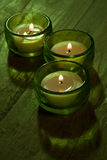 Three Candles. Three lit candles with green gelatin filter on wooden top Royalty Free Stock Photo