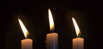 Three candles. Three lit wax candles on a black background Stock Image
