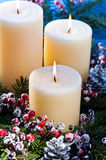 Three candles in an advent flower arrangement Royalty Free Stock Photos