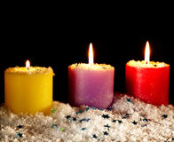 Three candles with artificial snow. Stock Photo