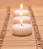 Three candles on a bamboo carpet Stock Photography