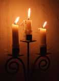 Three candles burning in a 13th century English parish Church Stock Photo