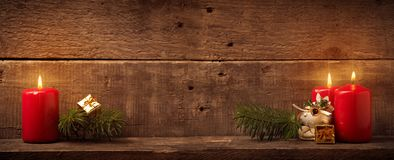 Three candles on rustic wood Stock Photos