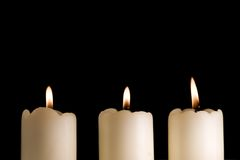 Three Candles Burning2. Three white candles lined up saucer isolated on black Royalty Free Stock Photos