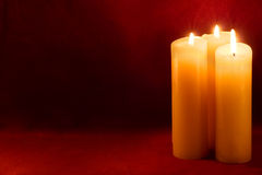 Three candles on carmine. Three burning yellow-white candles on dark red background Royalty Free Stock Photography