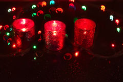 Three candles on dark. Three red candles, sparkling lights in the background etmnom. Multicolored bokeh hearts Royalty Free Stock Image