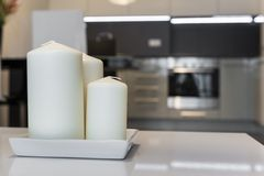 Three candles with defocus kitchen in background. Three candles with defocus modern kitchen interior design in background Royalty Free Stock Photography
