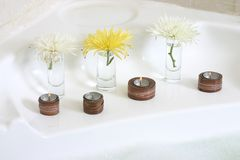 Three candles and flowers. Three lit candles and flowers decorating the white bath-tub Stock Images