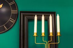Three candles on a green background, on the wall a clock and a frame Royalty Free Stock Image